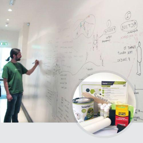 man using smart whiteboard paint white wall with kit contents on display