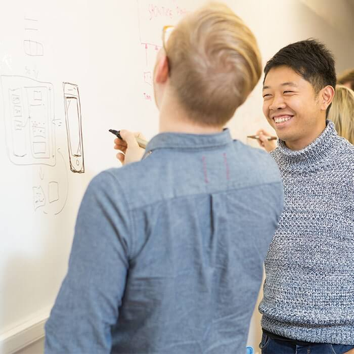 two men drawing up product designs on wall - whiteboard wallcovering