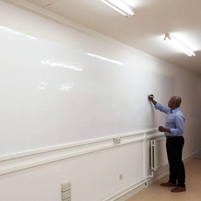 Man writing on glossy surface of Smart Whiteboard Wallpaper
