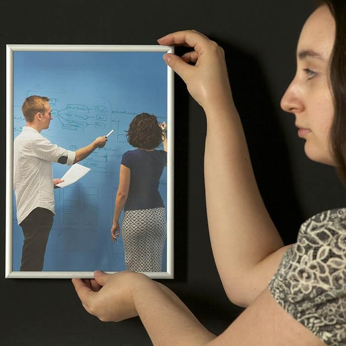 Woman hanging up frame on Super Magnetic Paint coated wall